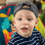 Male toddler wearing a blue and white striped t-shirt and baseball cap on backwards